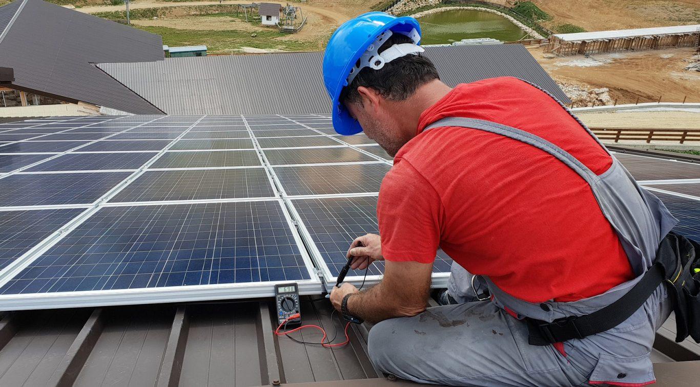 installateur répare des panneaux solaires sur un toit